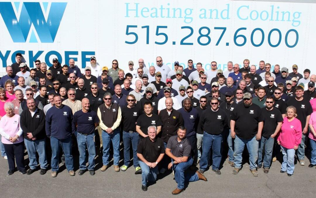 60+ Wyckoff employees posing for a picture during midday in front of a large Wyckoff semi with the Wyckoff logo and phone number displayed on the side of the truck