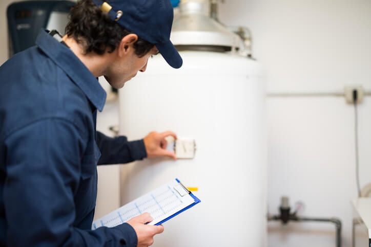 Male worker in a navy blue outfit and hat holding a clipboard adjusting a white hot water heater