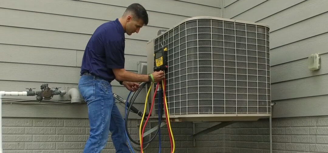 Man standing next to AC unit outside holding onto red and yellow lines connected to a gauge manifold