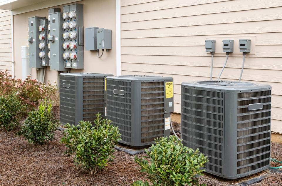 Three AC dark gray AC units outside of a building with cream siding
