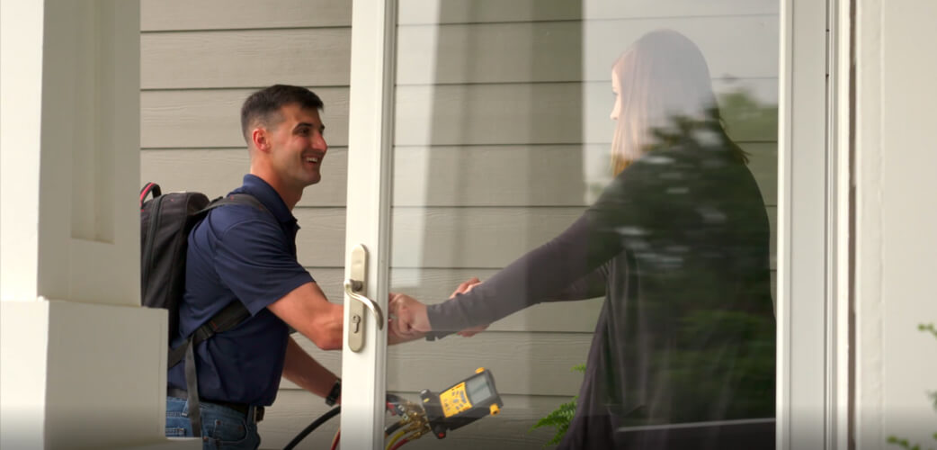 A man wearing a blue polo and backpack smiling and shaking hands with a woman who is holding a glass door open for him to enter