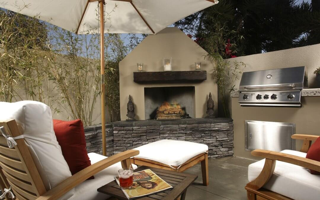 an outdoor patio equipped with a grill, chairs, and fireplace in a backyard