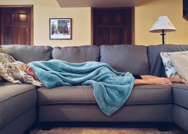A person covering themselves with a teal blanket while laying down on a large gray couch