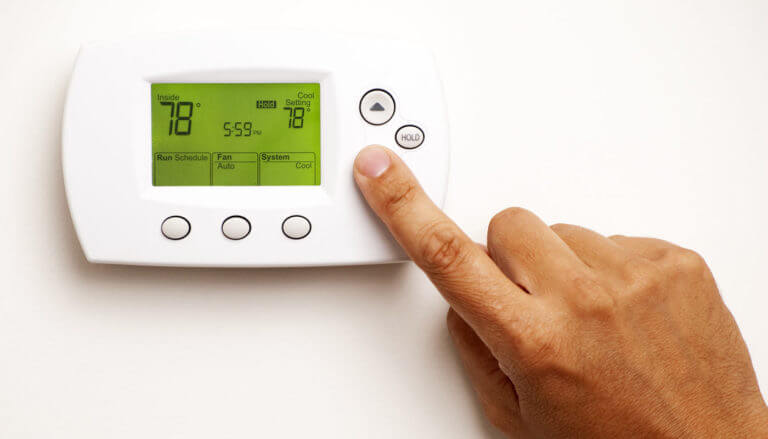 A person's hand click the down arrow on a white thermostat on a wall showing a temperature of 78 degrees