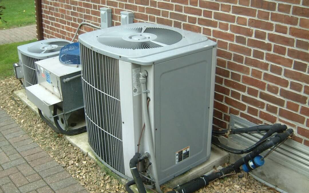 outdoor air conditioning unit on the ground next to brick exterior of a home