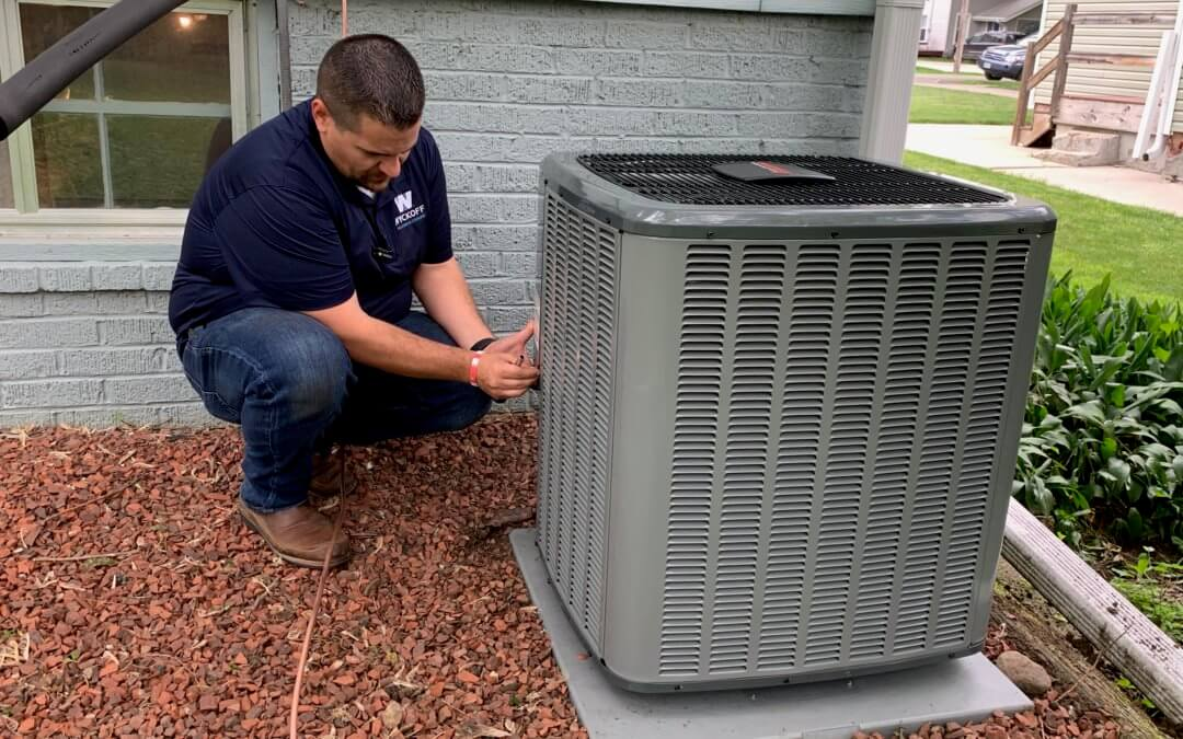 wyckoff heating and cooling technician squatting next to an outdoor air conditioner unit next to a residential home