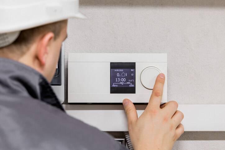 HVAC technician adjusts a programmable thermostat