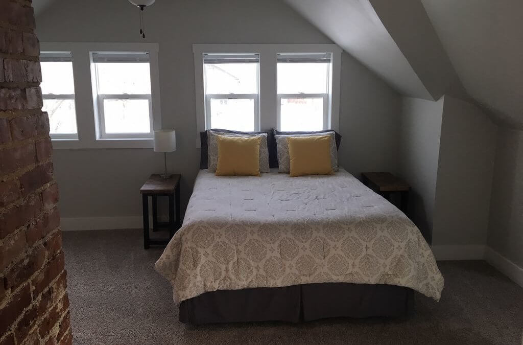 second floor bedroom of a home with a bed and side tables