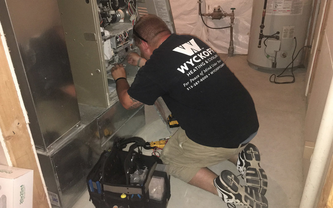 Brandan is wearing khaki shorts and a black shirt with a Wyckoff logo on the back and is on his knees repairing a furnace unit in a homeowner's basement